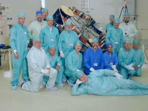 """An international AMSAT team (from 6 of the 14 countries involved in the project) pose in their """"bunny suits"""" in the ArianeSpace clean room facility in Kourou, French Guiana. The satellite is AMSAT's Phase 3-D which later became AMSAT OSCAR 40 on orbit."""