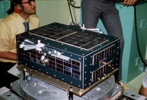 "AMSAT-OSCAR 6 undergoes shake testing.  Note the stowed ""carpenter's rule"" 10 Meter antenna."