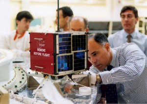 """Prior to launch, Dr. Dino Lorenzini, KC4YMG, pPerforms a """"fit check"""" on the """"Eyesat"""" satellite that later became AMSAT-OSCAR 27 on orbit. Note the black and white paint on the spacecraft's antennas."""