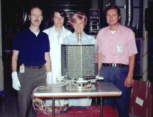 """Members of the AO-7 project team pose with the fruits of their labor. From left are Dick Daniels, W4PUJ (SK); Jan King, W3GEY; """"hired hand"""" Marie Marr and AMSAT Founding President Perry Klein, W3PK"""