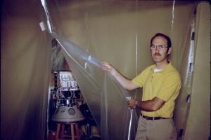 "Dick Daniels, W4PUJ (SK), displays a partially assembled AMSAT-OSCAR 8 in his basement ""clean room""."