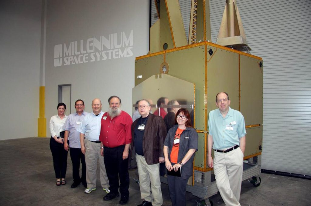 (L-R) Sonya Rowe, KK4NLO; Jerry Buxton, N0JY; Bob McGwier, N4HY; Franklin Antonio, N6NKF; Tom Clark, K3IO; Michelle Thompson, W5NYV; and Phil Karn, KA9Q standing next to the Aquila M8 Bus flight article.